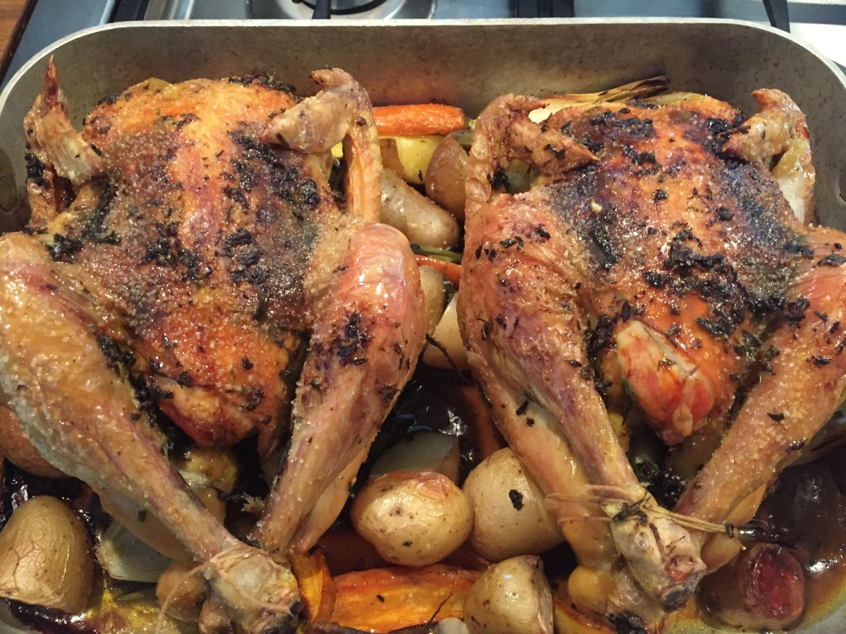 Helstekt kyckling med ört- och vitlökssmör. Rostad färskpotatis, morötter och lök